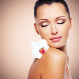 Fronte di bella donna con un fiore bianco dell'orchidea Fotografie Stock