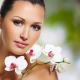 Fronte di bella donna con un fiore bianco dell'orchidea Fotografia Stock Libera da Diritti