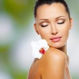 Fronte di bella donna con un fiore bianco dell'orchidea Fotografia Stock