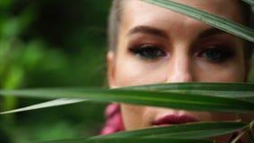 Fronte di bella giovane donna dietro la foglia di palma archivi video