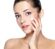 Fronte di bellezza di giovane donna con crema cosmetica su una guancica fotografie stock libere da diritti