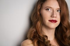 Fronte di giovane bella donna castana su fondo scuro nel rosso Fotografia Stock