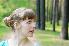 Fronte di giovane donna graziosa che distoglie lo sguardo nella foresta di estate Fotografia Stock