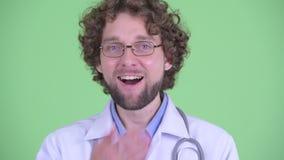 Fronte di giovane medico barbuto felice dell'uomo che sembra sorpreso video d archivio