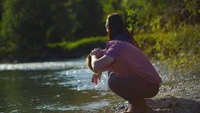 Fronte di lavaggio del viaggiatore del giovane con il fiume della montagna dell'acqua pulita 4 K video d archivio