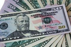 Fronte di menzogne delle banconote in dollari con un ritratto del presidente Fotografia Stock