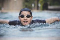 Fronte di nuoto asiatico del ragazzo nello stagno dello sport acquatico fotografia stock