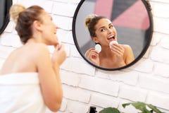 Fronte di pulizia della giovane donna in specchio del bagno fotografie stock libere da diritti