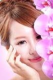 Fronte di sorriso della donna con i fiori dell'orchidea Fotografia Stock