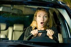 Fronte di spavento della donna che conduce automobile Immagine Stock