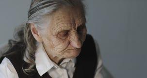 Fronte di una donna anziana con le grinze profonde che beve caffè video d archivio