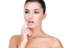 Fronte di una giovane donna graziosa con il dito alle labbra Immagini Stock