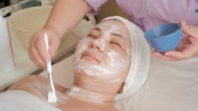 Fronte di una ragazza asiatica in un salone di bellezza L'estetista applica una crema bianca di massaggio all'area del collo di u