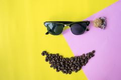 Fronte divertente di strato piano fatto dai chicchi di caffè nella forma dell'icona di sorriso e vetri di sole immagine stock