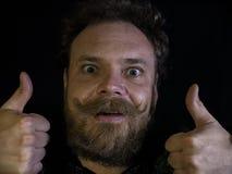 Fronte divertente di un uomo con una fine dei baffi e della barba su e mostrando i pollici su fotografia stock