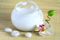 Fronte e crema per il corpo, ciottoli ed orchidea su bambù Immagini Stock