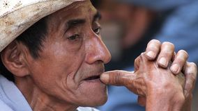 Fronte espressivo di un uomo anziano, gioca con le sue mani mentre riposa nella via nel mercato del villaggio di Xilitla video d archivio