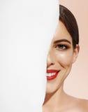 Fronte felice della donna chiuso per una metà con una carta Immagini Stock