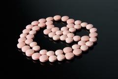 Fronte felice delle pillole rosa sul nero Fotografia Stock Libera da Diritti