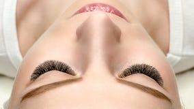 Fronte femminile con le estensioni del ciglio, pelle ben curato, vista superiore, fine su, fuoco selettivo fotografie stock