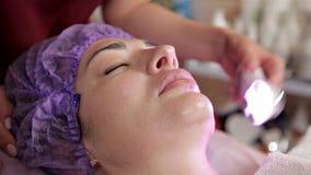 Fronte femminile, maschera del collagene Macchina per il rafforzamento della pelle Medicina estetica Scoloramento della pelle del stock footage