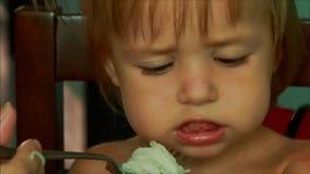 fronte grazioso della bambina che mangia maccheroni con le mani della forcella stock footage
