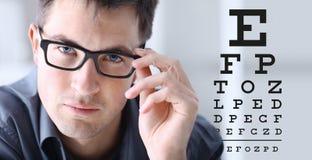 Fronte maschio con gli occhiali sul fondo del grafico di prova di vista Fotografia Stock Libera da Diritti