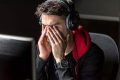 Fronte maschio esaurito sereno dello sfregamento allo scrittorio Immagine Stock