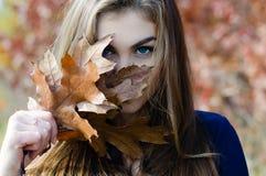 Fronte nascondentesi della bella donna dietro la foglia di marrone di autunno Fotografia Stock Libera da Diritti
