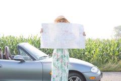 Fronte nascondentesi della donna con la mappa dal convertibile contro il chiaro cielo Fotografia Stock