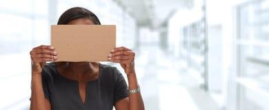 Fronte nascondentesi della donna di affari con cartone Fotografia Stock