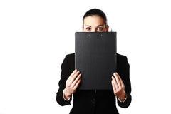 Fronte nascondentesi della donna di affari dietro il dispositivo di piegatura nero Fotografia Stock