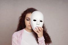 Fronte nascondentesi della ragazza triste dietro la maschera Fotografie Stock Libere da Diritti
