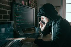 Fronte nascosto donna del pirata informatico facendo uso del telefono cellulare mobile Fotografia Stock Libera da Diritti