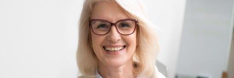 Fronte orizzontale di immagine della donna di affari invecchiata che sorride esaminando macchina fotografica fotografia stock