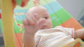 Fronte piccolo del bambino Chiuda su dell'infante sveglio che si trova sulla stuoia variopinta archivi video