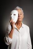 Fronte rivelante della donna matura seria dietro la maschera Fotografia Stock