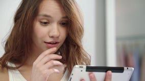 Fronte sorpreso della donna che esamina il computer della compressa Emozione colpita della donna video d archivio