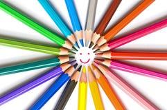 Fronte sorridente assorbito un cerchio delle matite di legno variopinte isolate su bianco, su arte della scuola e sul concetto di fotografia stock