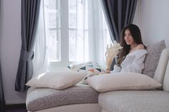 Fronte sorridente della bella giovane donna asiatica nella seduta bianca della camicia Immagini Stock Libere da Diritti