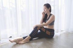 Fronte sorridente di giovane donna asiatica nel reggiseno di sport che parla sul telefono Immagine Stock