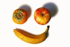 Fronte sorridente fatto della mela e della banana del cachi Fotografie Stock