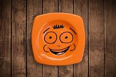 Fronte sorridente felice del fumetto sul piatto variopinto del piatto Fotografie Stock