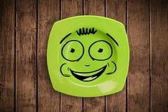 Fronte sorridente felice del fumetto sul piatto variopinto del piatto Fotografia Stock Libera da Diritti