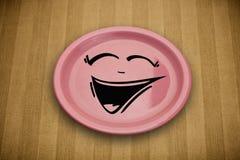 Fronte sorridente felice del fumetto sul piatto variopinto del piatto Immagine Stock