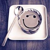Fronte sorridente su un vetro del latte evaporato per caffè Fotografia Stock