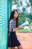 Fronte sorridente a trentadue denti asiatico del libro di scuola e della ragazza a disposizione con happ Immagini Stock Libere da Diritti