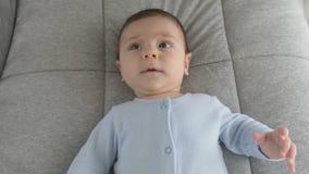 Fronte sveglio del bambino con gli occhi marroni Lo sguardo del bambino nel colpo del primo piano della macchina fotografica video d archivio