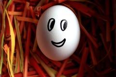Fronte sveglio di sorriso sull'uovo bianco in nido luminoso variopinto come simbolo di Pasqua Uovo festivo di Pasqua Progettazion immagini stock libere da diritti
