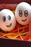Fronte sveglio di sorriso sulle uova bianche in nido luminoso variopinto come simbolo di Pasqua Uova festive di Pasqua Fotografia Stock Libera da Diritti